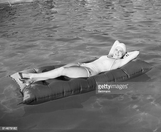 Sun bathing deluxe lying on a pneumatic mattress in the middle of a pool at Palm Springs CA pretty Olivia De Haviland Warners' player takes her ease...