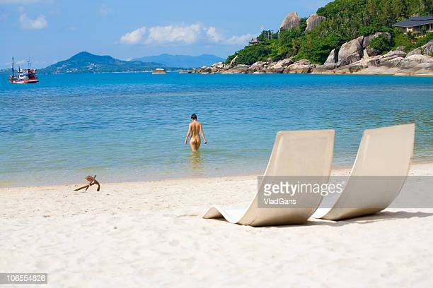 sun bed and girl on a sea beach - naturism stock photos and pictures