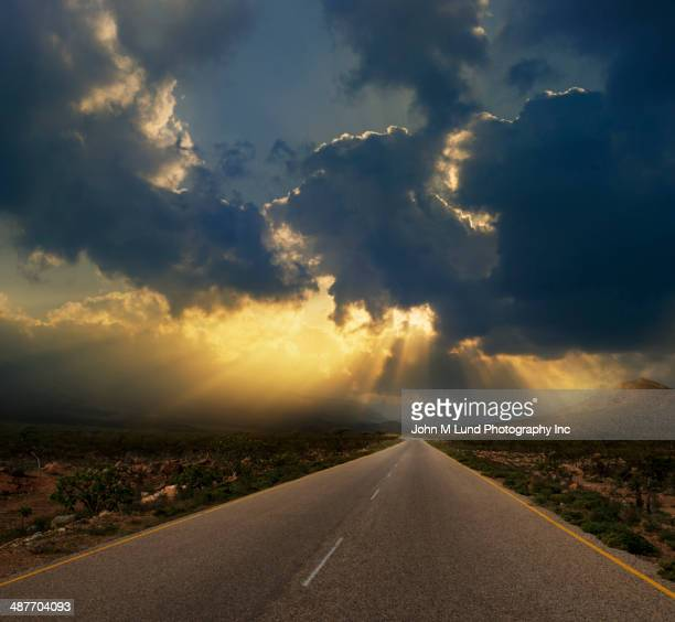 Sun breaking through dramatic clouds over landscape