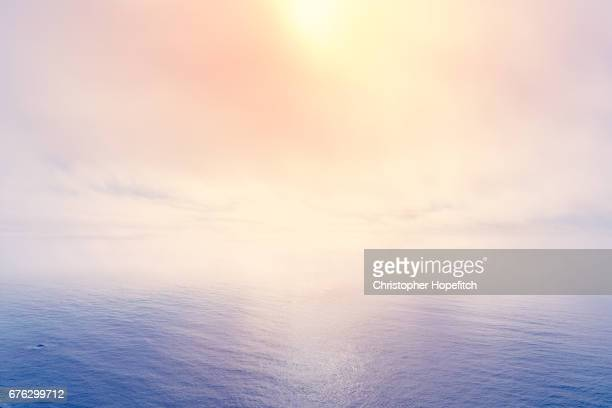 sun breaking through sea fog - paradise stock pictures, royalty-free photos & images