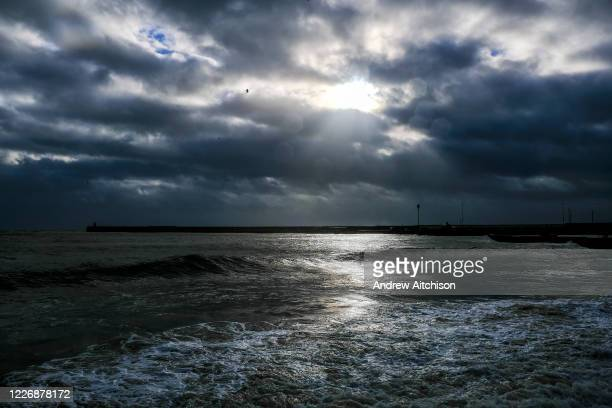 Sun breaks through dramatic clouds in the sky over Folkestone Harbour Arm during high tide from Sunny Sands Beach on 8th December 2018 in Folkestone...