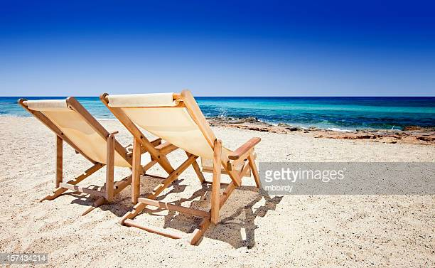 Sun chairs on sandy beach