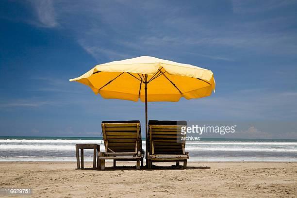 sun chairs with yellow umbrella
