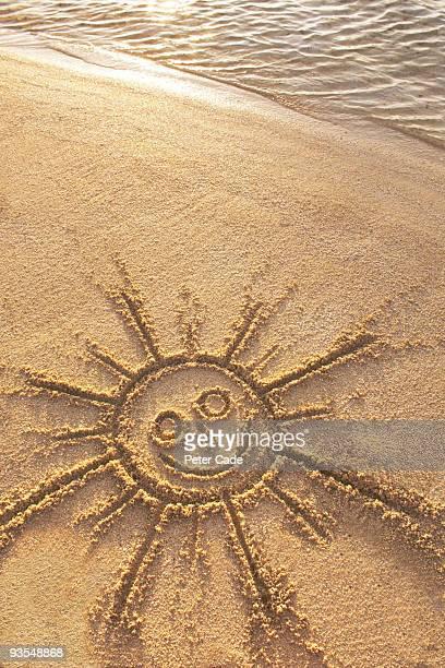 sun drawn in sand on beach by sea