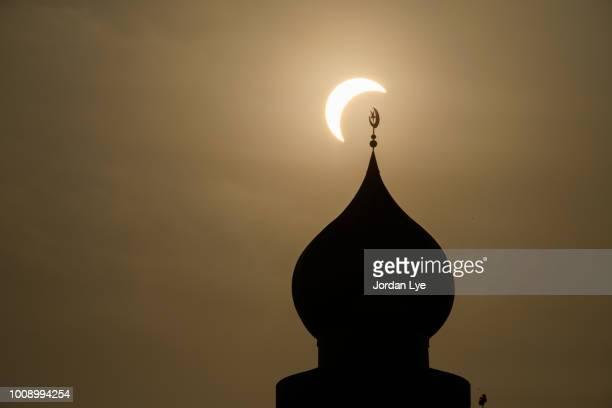 Sun eclipse over a mosque