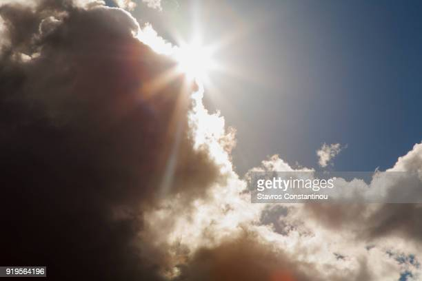 sun emerging from behind a dark cloud after a storm - appearance stock photos and pictures