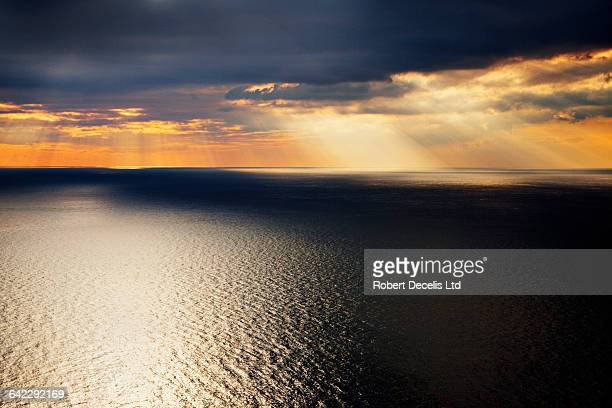 Sun emerging through black clouds over the sea