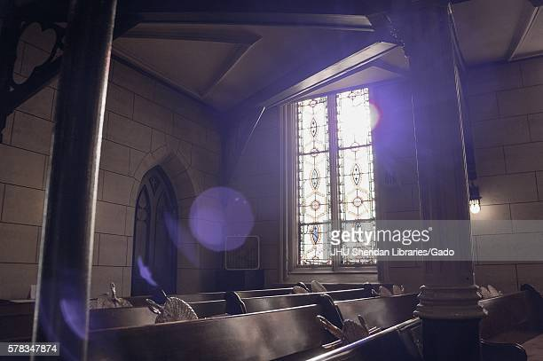 Sun filters through the stained glass of an old church, creating shadows on the pews with woven fans in their holders, Baltimore, Maryland,...