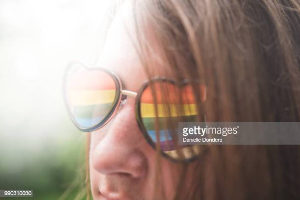"sun flare and reflection of rainbow pride flag in young person's heart-shaped glasses - ""danielle donders"" stock pictures, royalty-free photos & images"