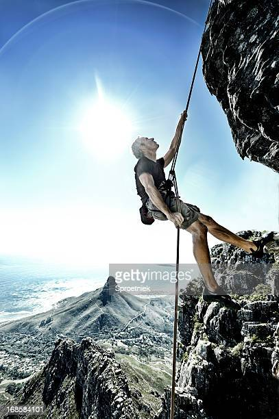 Sun flares surround abseiling climber on Table Mountain