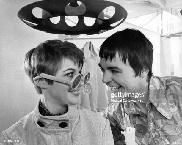 Sun glass wearing Adrienne Posta smiling at Barry Evans in a scene from the film 'Here We Go Round The Mulberry Bush' 1968