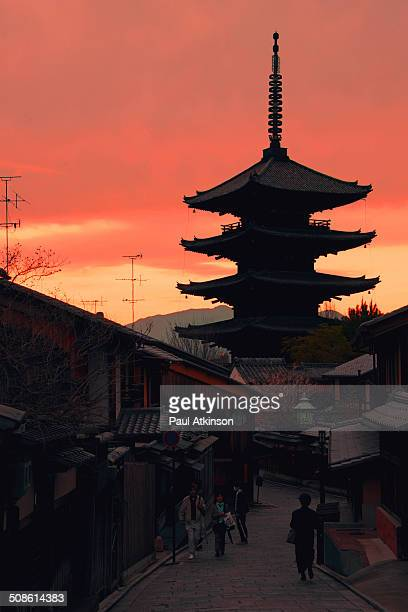 Sun goes down behind a temple pagoda in the city of Kyoto Japan