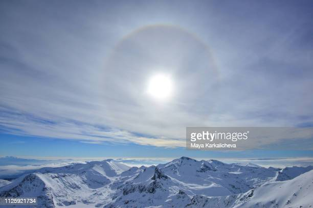 sun halo over snowcapped mountain range - pirin national park stock pictures, royalty-free photos & images