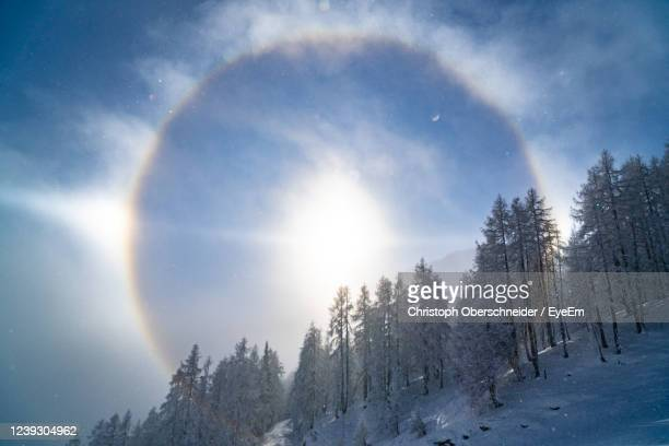 sun halo / sundogs optical phenomenon in winter wonderland, zauchensee ski resort, salzburg, austria - light natural phenomenon stock pictures, royalty-free photos & images