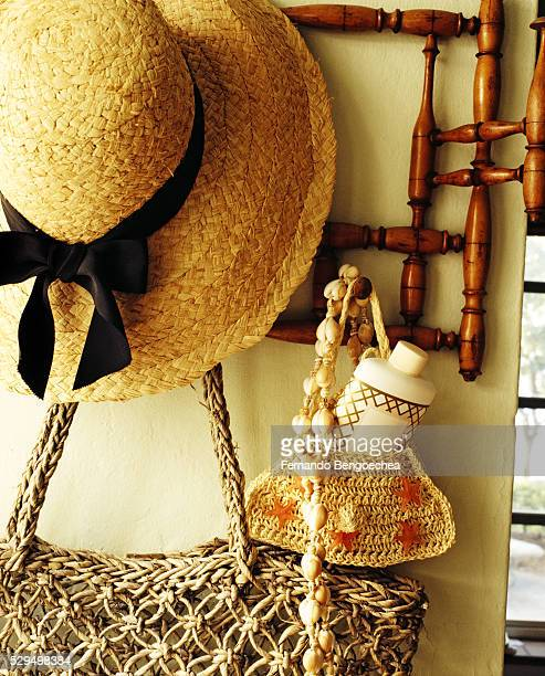 sun hat, bag, and macrame pouch with lotion bottle hang on spindle wall rack - fernando bengoechea stock pictures, royalty-free photos & images