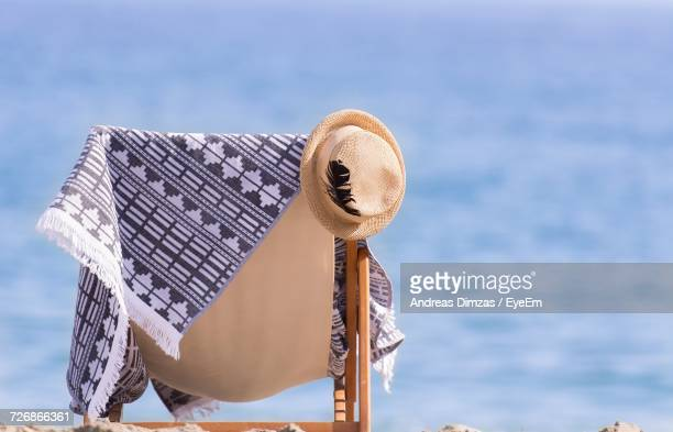 Sun Hat With Towel On Empty Deck Chair At Beach