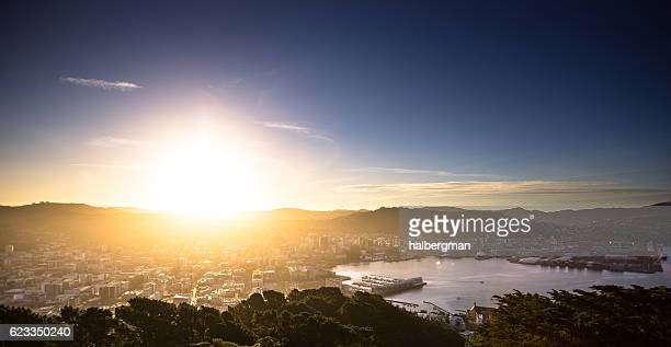 sun hitting the horizon over wellington harbour - wellington new zealand stock photos and pictures