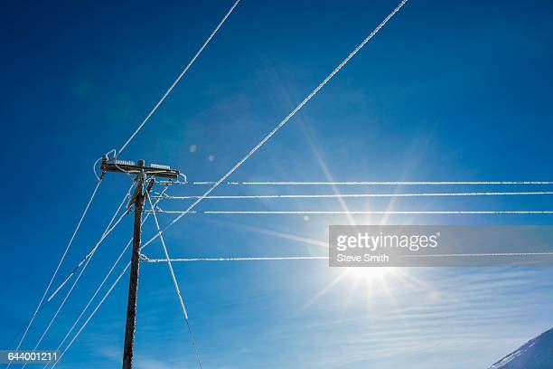 Sun in blue sky and frosty power lines