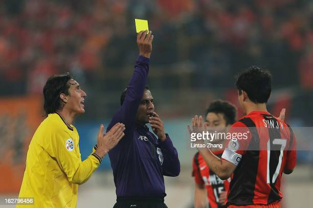 Sun Jihai of Guizhou Renhe is shown a yellow card by Referee Khalil Al Ghamdi with Cleo of Kashiwa Reysol during the AFC Champions League match...