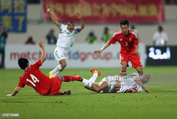 Sun Ke of China tackles Ahmed Yaseen Gheni of Iraq during the Asian Cup Qualification match between China and Iraq at the AlSharjah Stadium on March...