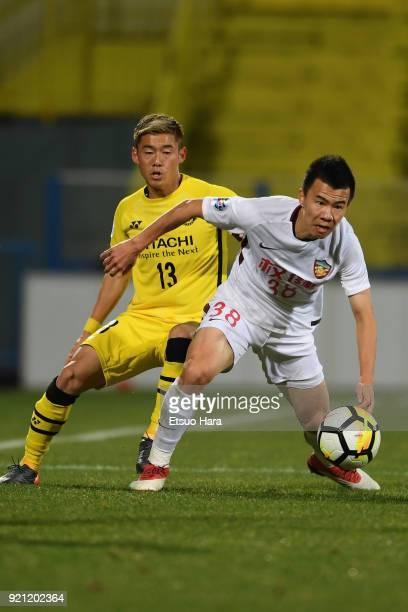 Sun Ke of Tianjin Quanjian controls the ball under pressure of Ryuta Koike of Kashiwa Reysol during the AFC Champions League match between Kashiwa...