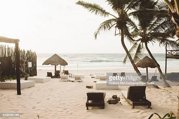 Sun loungers and sun shades on beach, Tulum, Mexico