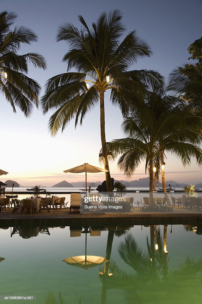 Sun Loungers And Sunshades By Swimming Pool At Dusk Stock ...