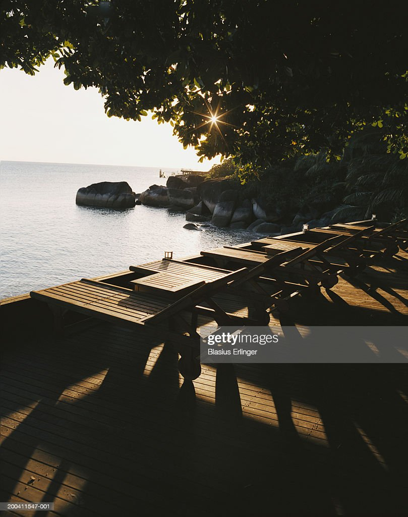 Sun loungers on terrace overlooking sea : Stockfoto