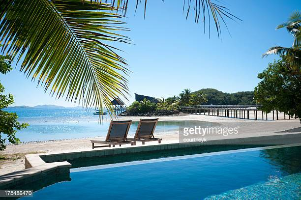 2 sun lounges beside a pool with beach