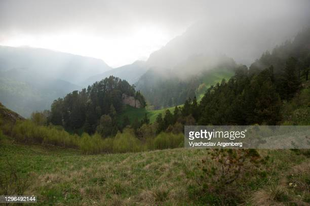 sun obscured by clouds, sunset in shisha valley, caucasus mountains - argenberg stock pictures, royalty-free photos & images