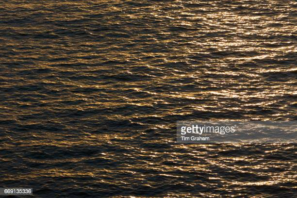 Sun on water close up of ripples gentle waves and sunlight reflecting on the surface of the ocean on September 25 2015 near Portsmouth United Kingdom
