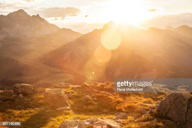 sun over dolomites mountains - lens flare stock pictures, royalty-free photos & images
