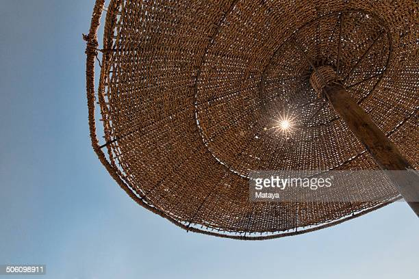 Sun peeking through beach umbrella