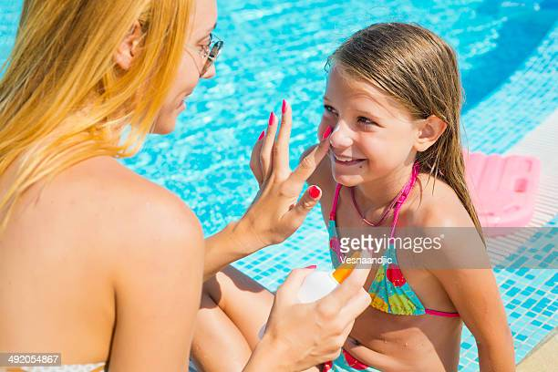 sun protection at pool - girls sunbathing stock photos and pictures