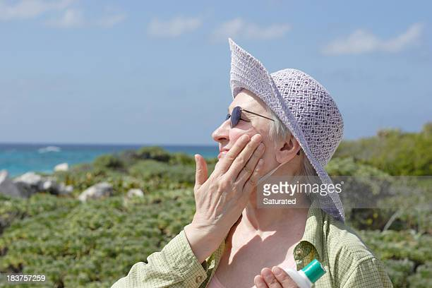 Sun Protection - Woman in Sunhat and Sunglasses Applying Sunscreen