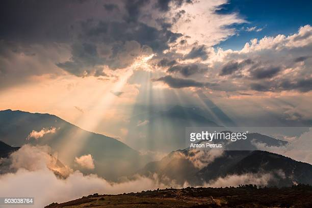 sun rays breaking through the clouds over a mountain - anton petrus stock pictures, royalty-free photos & images