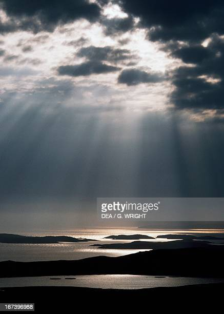 Sun rays filtering through clouds at sunset over Burra Islands Shetland Islands Scotland United Kingdom