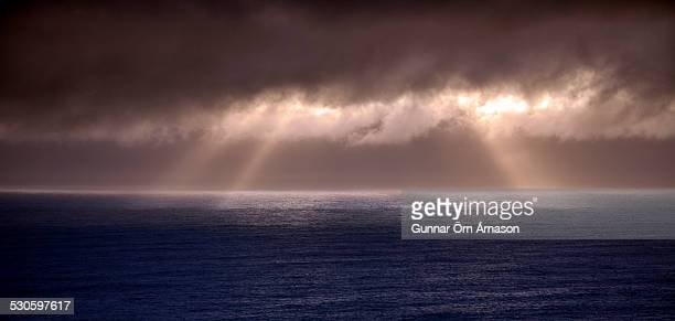 sun rays over water - gunnar örn árnason stock pictures, royalty-free photos & images
