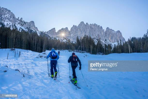 """sun rays passing through the """"grossmutterloch"""" (or grandmother's hole) gastlosen mountain range - two non recognizable touring skiers arriving on site to enjoy the phenomenon - light natural phenomenon stock pictures, royalty-free photos & images"""