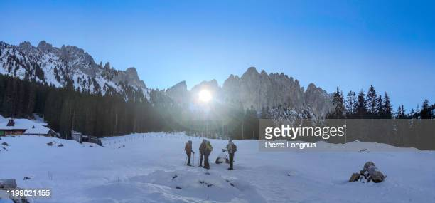 """sun rays passing through the """"grossmutterloch"""" (or grandmother's hole) - non recognizable snowshoe hikers attending the phenomenon - light natural phenomenon stock pictures, royalty-free photos & images"""