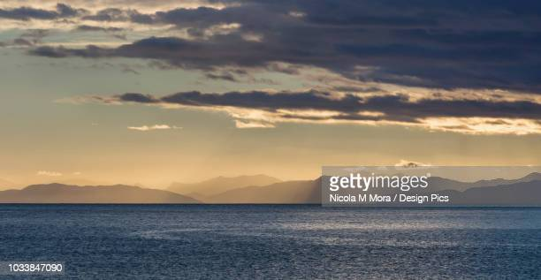 Sun rays shining through clouds over the mountains and ocean at sunrise, Abel Tasman National Park