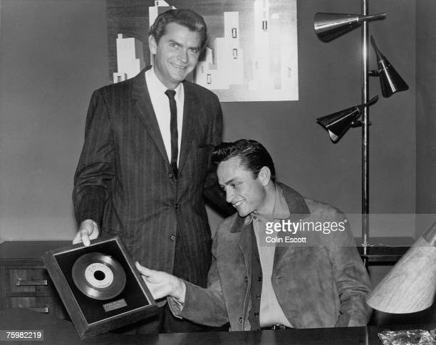 Sun Records founder Sam Phillips poses for a portrait with country singer/songwriter Johnny Cash as he gives him a framed record of the song 'I Walk...