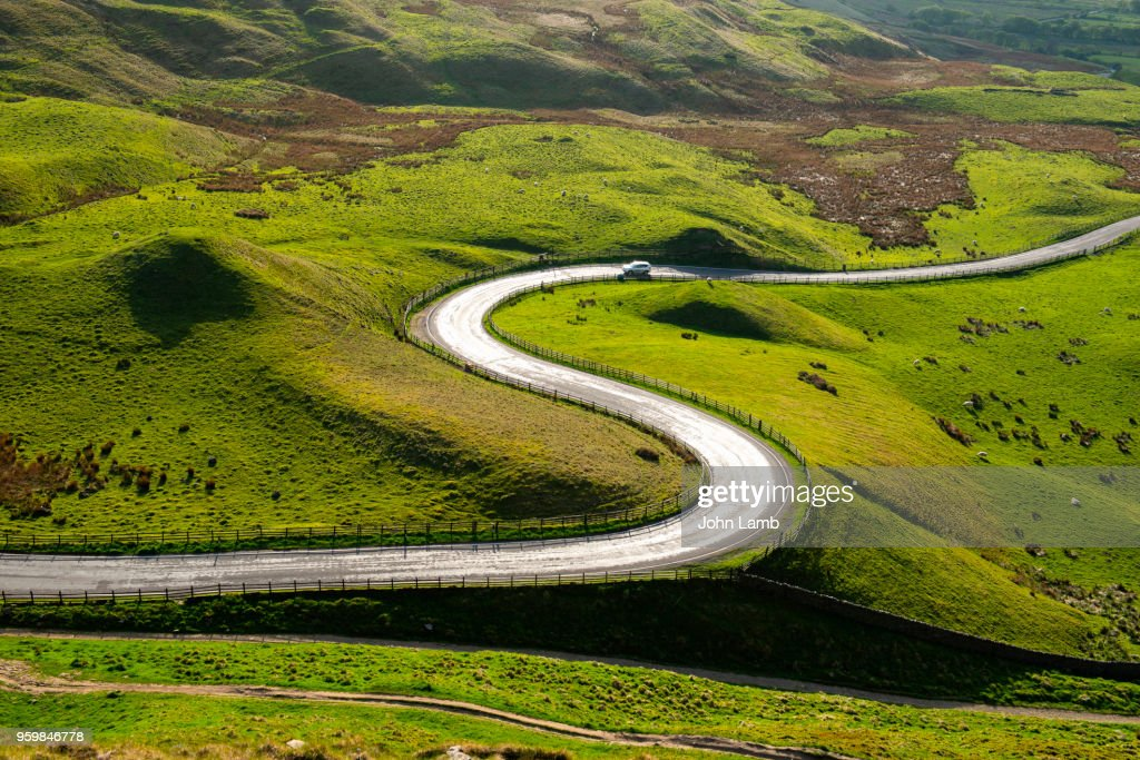 Sun reflecting on sinuous curving road in the English Peak District : Stock-Foto