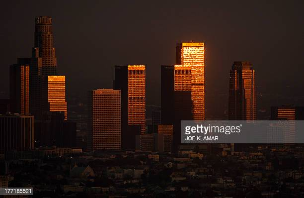 A sun reflects on highrises in downtown during sunset in Los Angeles California on August 21 2013 AFP PHOTO /JOE KLAMAR