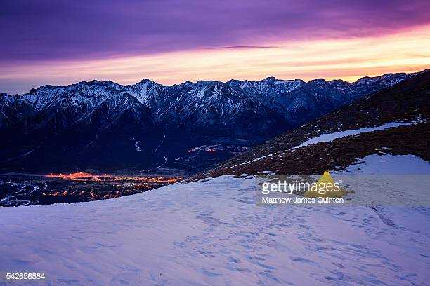 Sun rises over small yellow tent perched in saddle of snowy mountain with pretty pink sky and lights of mountain town below