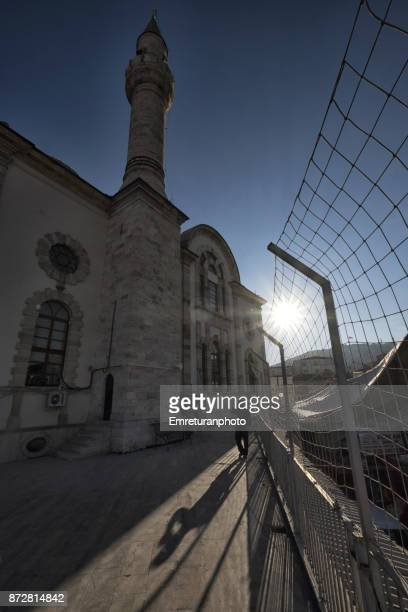 sun rising behind a man standing in front of kestanepazari mosque in kemeralti,izmir. - emreturanphoto stock pictures, royalty-free photos & images