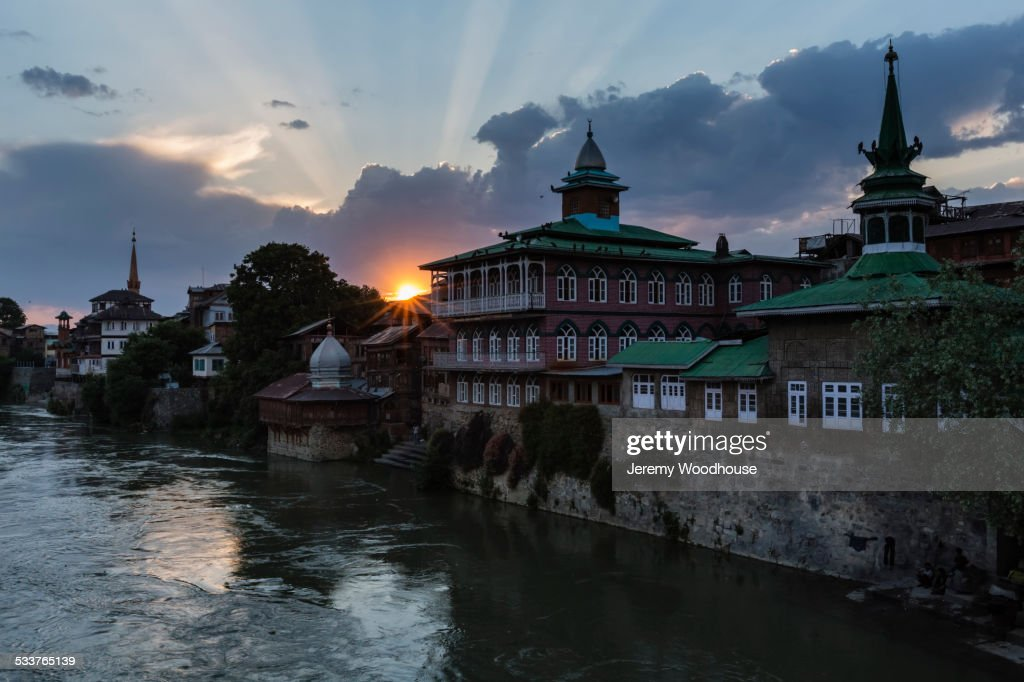 Sun rising over ornate buildings and village waterfront : Foto stock