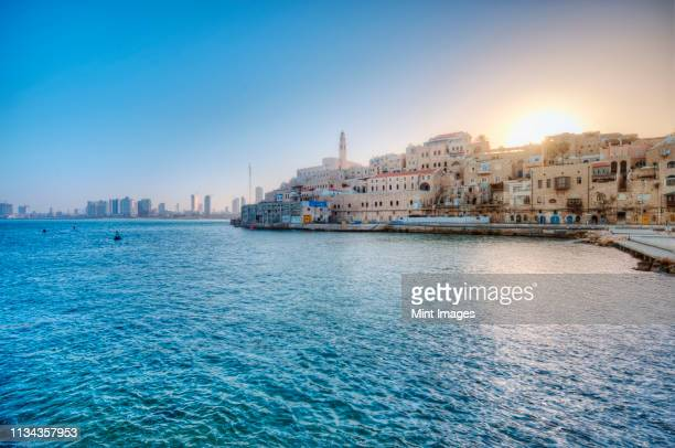 sun rising over waterfront town, israel - israel stock pictures, royalty-free photos & images