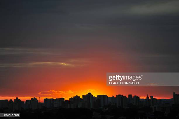 sun sets behind buildings - claudio capucho stock photos and pictures