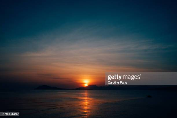 Sun sets behind the mountains as seen from the coast of Ende, Flores, Indonesia.